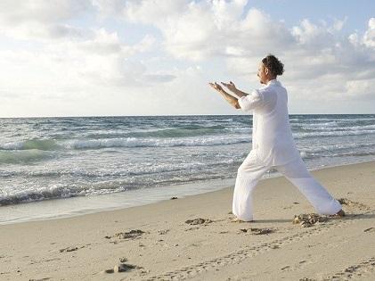 man meditating by the beach