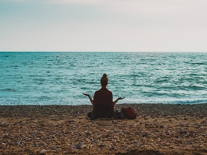 woman yoga meditating sitting beach
