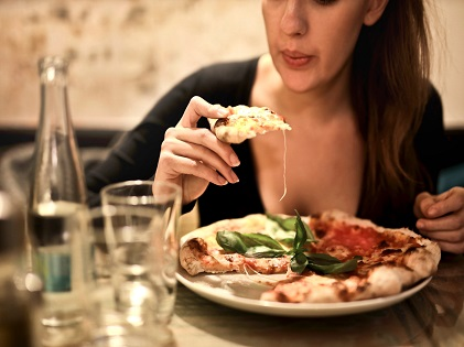 woman-holds-sliced-pizza-seats-by-table-with-glass